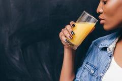 Primo piano della donna di colore con vetro di succo d'arancia Immagine Stock
