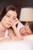 Primo piano della donna infelice che si trova a letto sollecitata Immagine Stock