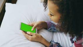 Primo piano della donna riccia della corsa mista che si trova a letto a casa facendo uso dello smartphone con lo schermo verde Fotografia Stock Libera da Diritti