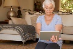 Primo piano della donna senior che si esercita con una compressa digitale a casa Fotografia Stock