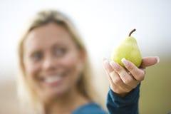 Primo piano della donna sorridente che tiene una pera fotografia stock libera da diritti