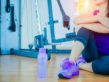 Primo piano della donna stanca che riposa dopo l'allenamento con le attrezzature di forma fisica nel fondo Fotografia Stock