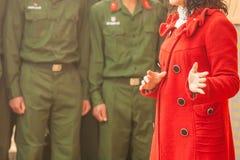 Primo piano della donna vietnamita di professore in cappotto lungo rosso che parla al giovane soldato vietnamita immagine stock