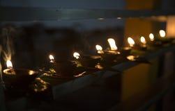 Primo piano della fiamma di candela Molte candele in un tempio buddista Religi Fotografie Stock