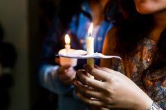 Primo piano della gente che tiene veglia della candela nella speranza di ricerca scura immagine stock libera da diritti