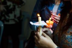 Primo piano della gente che tiene veglia della candela nella speranza di ricerca scura fotografie stock libere da diritti