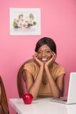 Primo piano della giovane donna felice che per mezzo del computer portatile Fotografie Stock