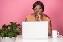 Primo piano della giovane donna felice che per mezzo del computer portatile Immagine Stock