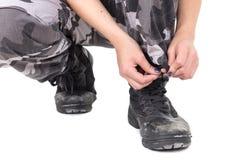 Primo piano della giovane donna militare che lega i suoi stivali Fotografie Stock Libere da Diritti
