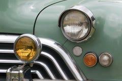 Primo piano della griglia e luci dell'automobile classica ristabilita Immagine Stock