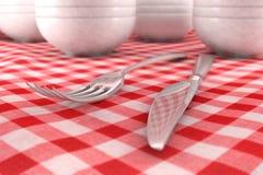 Primo piano della lama e della forcella su un panno di tabella rosso Fotografie Stock