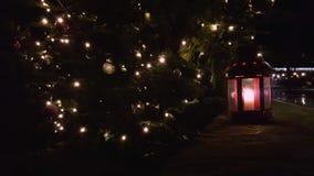 Primo piano della lanterna di Natale La lanterna rossa di Natale sta il unde sotto un abete di Natale Lanterna con la candela di  archivi video