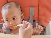 Primo piano della madre che alimenta neonata asiatica con un cucchiaio in alta c fotografie stock libere da diritti