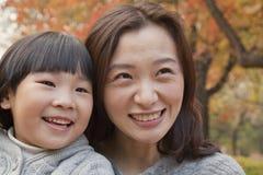 Primo piano della madre e della figlia che sorridono nel parco, autunno, ritratto Fotografia Stock Libera da Diritti
