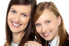 Primo piano della mamma e della figlia che infiammano un sorriso Immagini Stock Libere da Diritti
