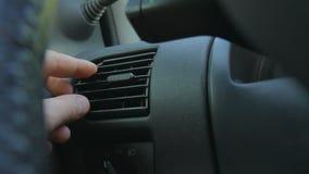 Primo piano della mano che regola gli sfiatatoi per cambiare direzione del vento dentro l'automobile Stato troppo fresco o troppo stock footage