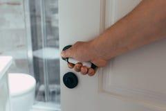 Primo piano della mano che tiene la maniglia della porta del metallo sulla porta di legno fotografia stock