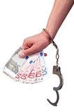 Primo piano della mano con le manette che tengono soldi su fondo bianco Fotografie Stock