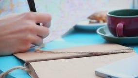 Primo piano della mano con le note di scrittura della penna, turista della donna in caffè che controlla mappa stock footage