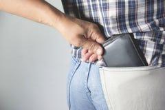 Primo piano della mano del ladro che ruba il portafoglio ad una donna fotografia stock libera da diritti