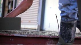 Primo piano della mano del muratore che sparge miscela di calcestruzzo archivi video