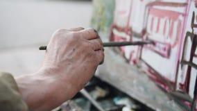 Primo piano della mano dell'artista con una spazzola in  archivi video