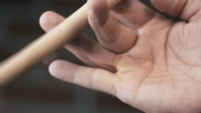 Primo piano della mano dell'uomo che volteggia le bacchette di legno azione Ginnastica della mano archivi video