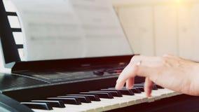 Primo piano della mano dell'uomo di un esecutore di musica che gioca il piano dal lato stock footage
