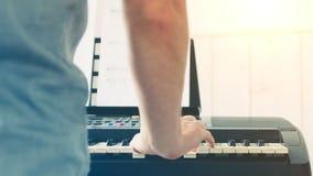 Primo piano della mano dell'uomo di un esecutore di musica che gioca il piano dalla parte posteriore archivi video