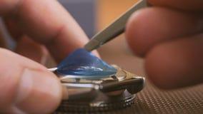 Primo piano della mano dell'uomo, rimuovente con l'autoadesivo protettivo delle pinzette con un nuovo orologio Disimballaggio del archivi video