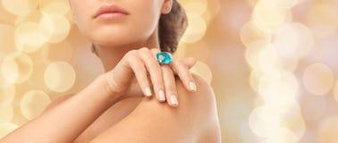 Primo piano della mano della donna con il grande anello blu del cocktail Fotografia Stock