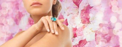 Primo piano della mano della donna con il grande anello blu del cocktail Immagini Stock