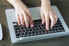 Primo piano della mano della donna di affari che scrive sul computer portatile keyboar Fotografia Stock