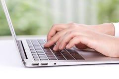 Primo piano della mano della donna di affari che scrive sulla tastiera del computer portatile Immagini Stock Libere da Diritti