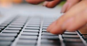 Primo piano della mano della donna di affari che scrive sulla tastiera del computer portatile Il primo piano di una femmina passa stock footage