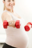 Primo piano della mano della donna incinta che tiene bilanciere rosso Fotografia Stock