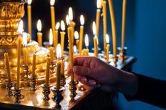 Primo piano della mano della ragazza che accende una candela Fotografie Stock