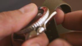 Primo piano della mano di un uomo che indossa una cinghia cachi di nylon sull'orologio di un operatore subacqueo meccanico video d archivio