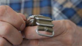 Primo piano della mano di un uomo, che inizia il meccanismo dell'orologio manuale, girante la corona con le vostre dita archivi video