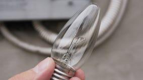Primo piano della mano di un uomo che tiene una lampada incandescente con il filamento di tungsteno bruciato archivi video