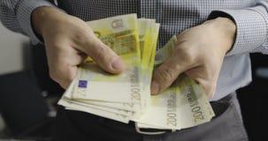 Primo piano della mano di un uomo d'affari che conta duecento euro fatture archivi video