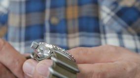Primo piano della mano di un uomo in una camicia di plaid che tiene ed osserva un orologio d'immersione su una cinghia di nylon stock footage