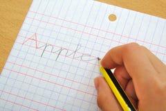 Primo piano della mano di una parola della mela di scrittura del bambino Fotografia Stock