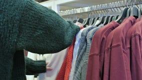 Primo piano della mano di una ragazza in un deposito che sceglie i vestiti che appendono sui ganci da vendere archivi video