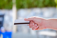 Primo piano della mano femminile che passa una carta di credito Fotografie Stock