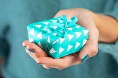 Primo piano della mano femminile che tiene un presente Fotografia Stock