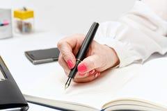Primo piano della mano femminile con il computer portatile, lo smartphone ed il taccuino Immagini Stock