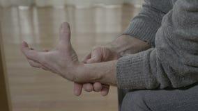 Primo piano della mano invecchiata dell'uomo anziano colpita dal dolore rheumatical - archivi video