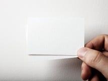Primo piano della mano maschio che tiene un affare di due bianchi fotografia stock libera da diritti