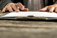 Primo piano della mano maschio circa per firmare una sottoscrizione o un'applicazione Immagini Stock Libere da Diritti